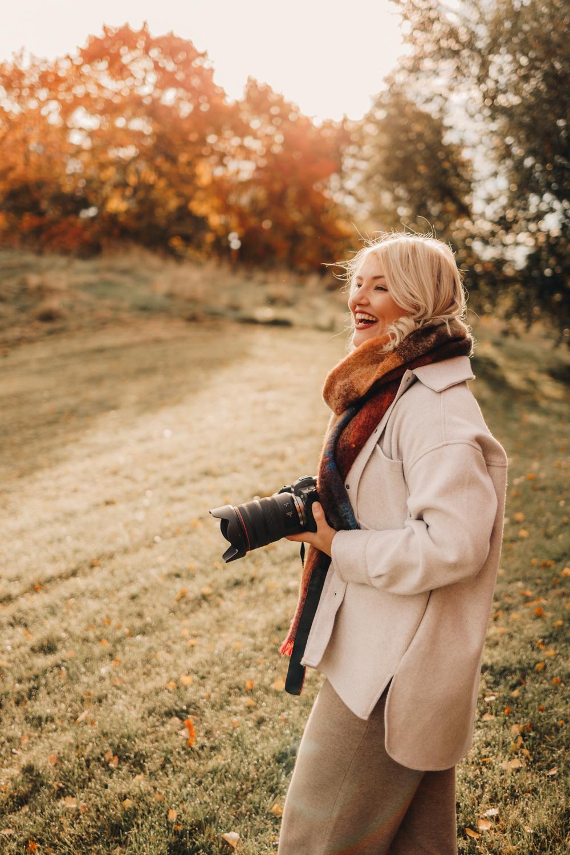Valokuvaaja Via Ramstén kameransa kanssa syksyisessä miljöössä